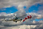 Helicopter Flying In Cloudy Sky. Airport Windsock On Cloudy Sky Background In Windy Weather Indicdro poster