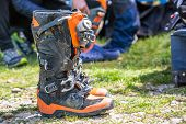 Постер, плакат: Protective Equipment For Motorsport With Spare Parts Stacked In A Van Background Shoes Close Up