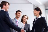 foto of business meetings  - Image of businessman and woman shaking hands at meeting - JPG