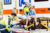 Emergency doctors caring for accident victim boy sitting on stretcher poster