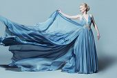 Full length portrait of a magnificent young woman in elegant long blue dress with lush skirt.  poster