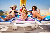 Cheers! Low Angle Shot Of Three Chics Sun Bathing Near The Pool On Striped Beach Chairs. Attractive  poster
