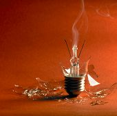 image of light-bulb  - broken upright light bulb with smoke and lots of shards in orange red back - JPG