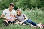Happy Young Family Enjoy Time Together Outside. Mom, Dad And Little Baby Daughter Resting In Nature. poster