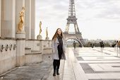 Happy Woman In Grey Coat Standing On Trocadero Square Near Gilded Statues And Eiffel Tower In Paris. poster