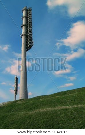 Two Floodlight Towers Between Sky And Earth
