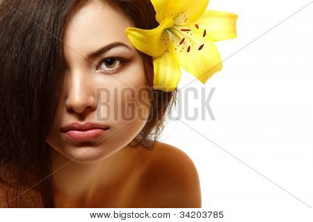 beautiful spa young multiracial woman with yellow flower lily in her hair. Isolated on white background