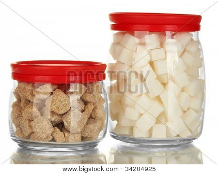 Jars with brown cane sugar lump and white lump sugar isolated on white