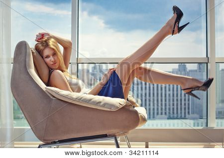 Joven mujer sentada en la silla en el fondo de la ventana.