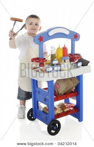 A young preschooler by his vendor stand holding a hot dog on the end of his tongs.  The stand's signs left blank for your text.  On a white background.