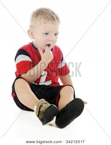 A young preschooler concerned about a tooth.  His mouth is opened wide with a finger feeling it.  On a white background.