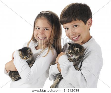 A brother and sister each happily holding a kitten.  On a white background.