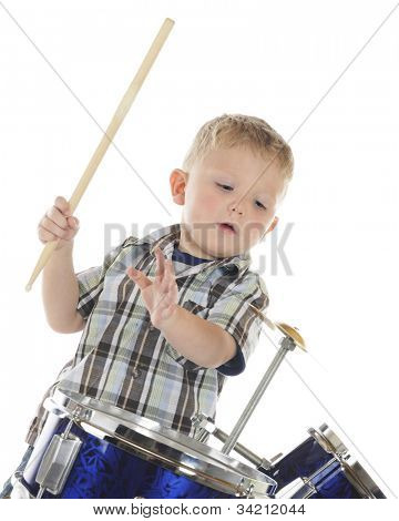 A young preschooler poised to strike the cymbal on his drum set.  On a white background.