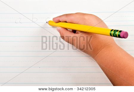 Education back to school concept with close up of child's hand writing alphabet on paper