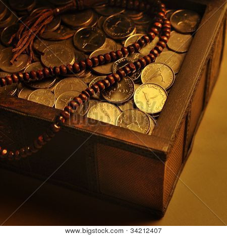 UAE Dirham coins in a trunk and wooden rosary