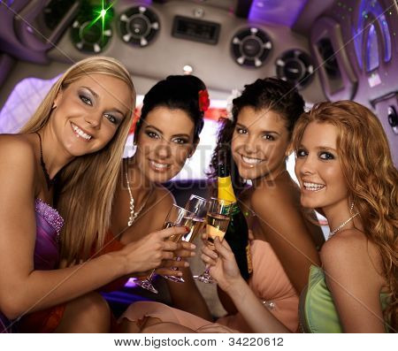 Happy women celebrating in limousine, smiling, looking at camera.