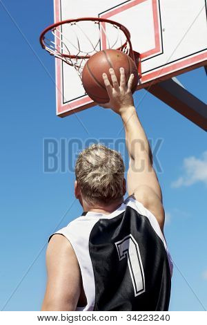 Basketball player throws ball in the basket