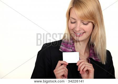 blonde businesswoman with downcast eyes showing business card