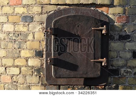 Rust door in brick wall