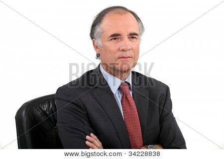 Senior businessman sat with his arms crossed