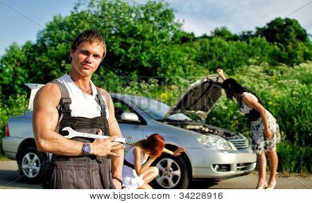 Portrait Of A Hadsome Mechanic With Two Women On A Background