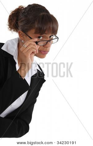 Critical woman peering over her glasses