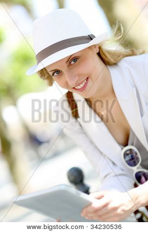 Beautiful city girl using tablet in town