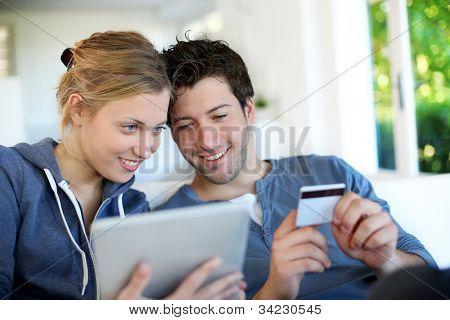 Feliz pareja joven haciendo compras en internet