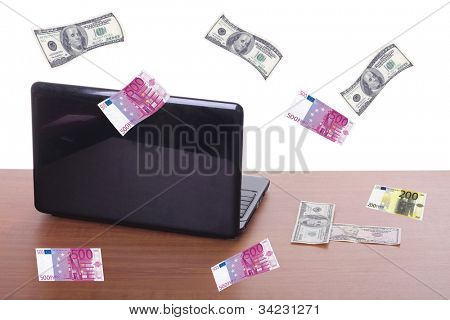 money flying and pouring out from a notebook computer