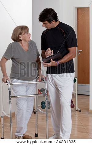 Patient with walker discusses his progress.