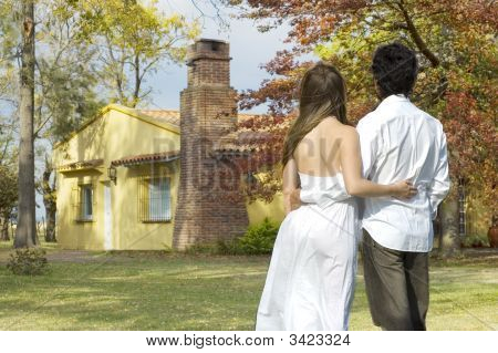 Young Couple Looking At A Farm House