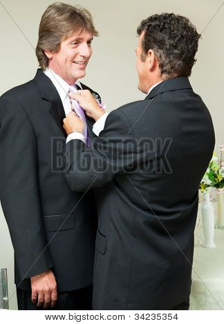 One groom straightens the other groom's tie at a gay marriage reception.