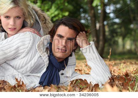 Couple lying among the autumn leaves