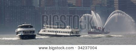 HOBOKEN, NJ - MAY 23: Two NY Waterway ferry's travel on the Hudson River past Fireboat John J. Harvey during the Parade of Sails on May 23, 2012 in Hoboken, NJ. The parade marks the start of Fleet Week.