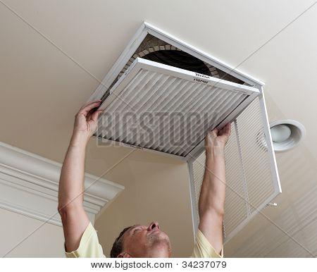 Filtro de ar condicionado de abertura de homem sênior no teto
