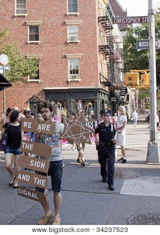 NEW YORK - JUNE 22: Supporters carry signs as they march past Christopher Street and Hudson St on the 8th Annual Trans Day of Action on June 22, 2012 in New York City.
