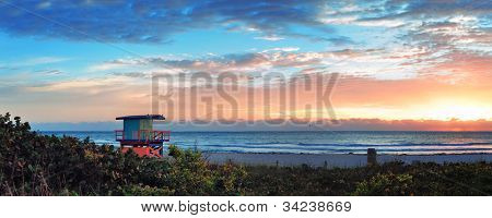 Miami South Beach sunrise panorama with lifeguard tower and coastline with colorful cloud and blue sky.