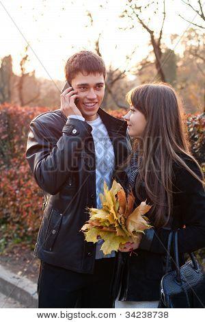 Pareja feliz en otoño al aire libre. Hombre hablando por teléfono móvil