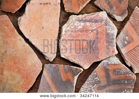 ancient Native American Indian (Anasazi) artifacts, several pottery fragments  on a wood background
