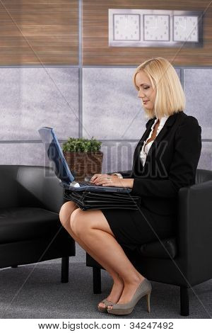 Pretty businesswoman sitting in office lobby, working on laptop computer in armchair, smiling.