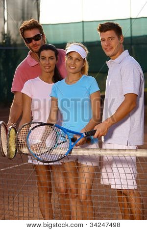 Young friends standing on tennis court, smiling.