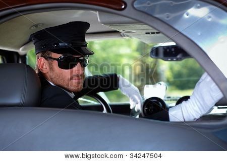 Young chauffeur in elegant automobile.