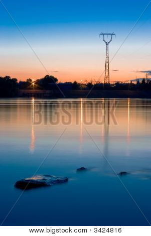 Powerline Near The River Against Sunset