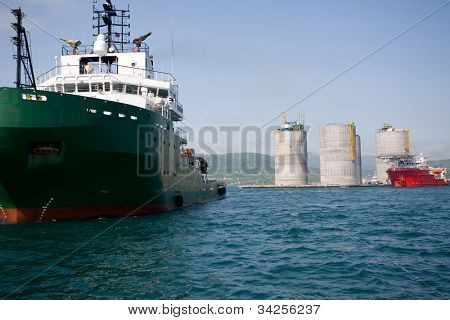 Ocean tugs at the base of offshore oil drilling platform. Sea Japan. Russian coast.