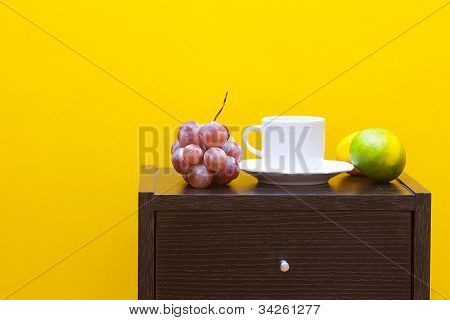 Bedside Table,fruits And Cup Against A Yellow Wall In The Apartment