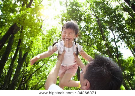 happy little girl with father in the green forest at morning