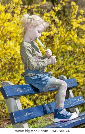 little girl with a lollipop sitting on bench in spring