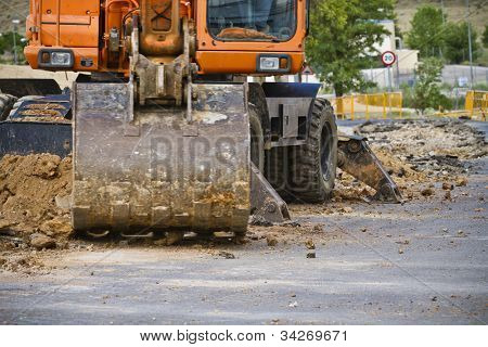 Closeup skid steer loader excavator at road construction work