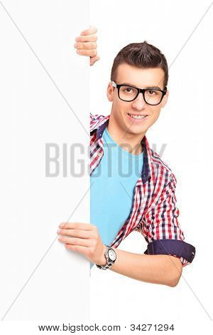 A smiling handsome male posing behind a white panel isolated against white background