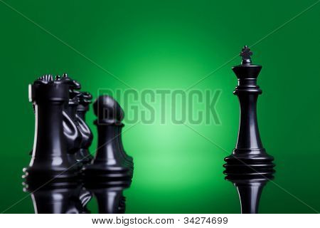 black king leading his army - side view of a black king standing in front of the rest of the chess pieces on green background